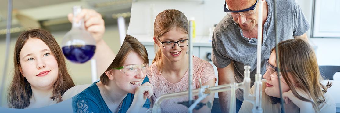 Drei Schülerinnen mit Lehrer im Chemieunterricht