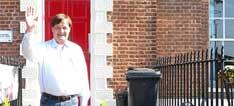 Detlef Kullmann winkend vor seiner Unterkunft, einem typisch englischem Reihenhaus