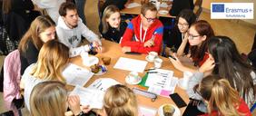 Jugendliche sitzen um einen Tisch und sprechen miteinander