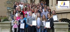 Kindergruppe auf Schultreppe mit Urkunden in der Hand