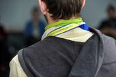 Hinterkopf und Schultern eines Mannes von hinten, um den Hals eine Erasmus+ Schlüsselkette